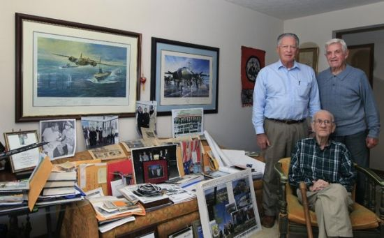 In this Dec. 1, 2011 photo, Maj. Thomas Griffin, seated, poses next to a couch covered with memorabilia from World War II at his home in Cincinnati with Ray Hughes, left, a veteran of the Strategic Air Command, and fellow WW II veteran Bill Barr. Griffin was a navigator on one of the planes used in Doolittle's raid on Japan in 1942. Coming just four months after the Imperial Japanese Navy savaged the U.S. Pacific Fleet at Pearl Harbor, the Doolittle raid on Japan's home did little damage, but lifted the spirits of Americans and electrified a world at war. (AP Photo/Al Behrman)