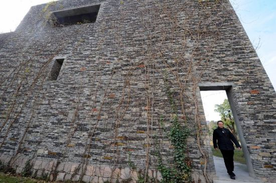 Wang Shu walks past a rubble-built elevation at the Xiangshan campus of the China Academy of Art in Hangzhou, capital of east China's Zhejiang Province, Dec. 9, 2011. (Xinhua/Li Xiaoguo)