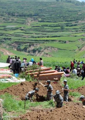 Rescuers dig holes to place coffins during the funeral held for victims killed in the deadly earthquake in Yongguang Village, Meichuan Township, Minxian County, northwest China's Gansu Province, July 23, 2013. Twelve bodies buried in ruins in the village were digged out, and their relatives held funerals for them on Tuesday. (Xinhua/Luo Xiaoguang)