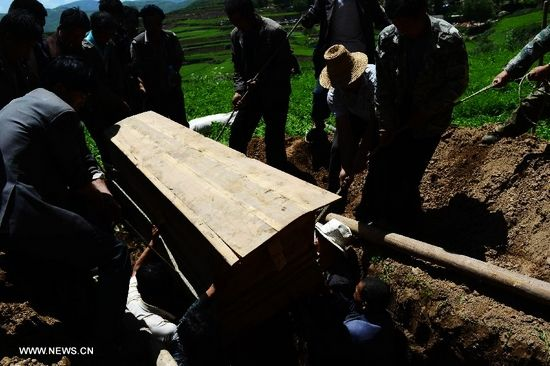 People place a coffin in to a hole during a funeral held for an 84-year-old villager killed in the dealy earthquake in Lalu Village, Hetuo Township, Minxian County, northwest China's Gansu Province, July 23, 2013. The death toll in the 6.6-magnitude earthquake that hit Gansu has risen to 94, local authorities said Tuesday. (Xinhua/Jin Liangkuai)