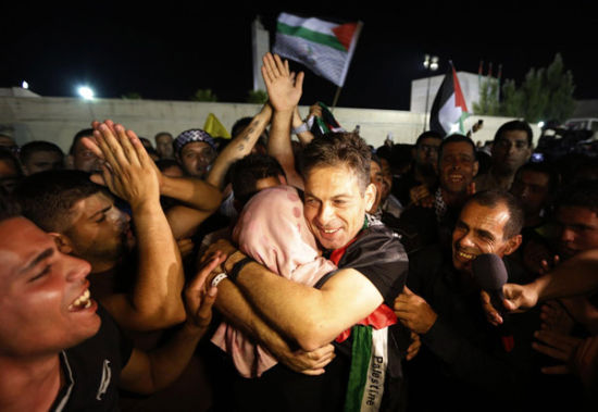A freed Palestinian prisoner hugs a relative after his arrival in the West Bank city of Ramallah August 14, 2013.[Photo/Agencies]