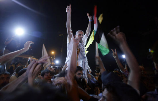 A freed Palestinian prisoner gestures upon his arrival near Erez crossing, between Israel and northern Gaza Strip, early August 14, 2013.[Photo/Agencies]