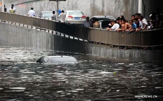 People look at a car almost submersed by water on a waterlogged street in Tiexi District of Shenyang, capital of northeast China's Liaoning Province, Aug. 16, 2013. Some parts of Shenyang were waterlogged due to downpour caused by thunderstorms Friday. (Xinhua/Huang Jinkun)