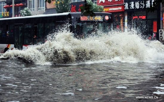 A bus moves on waterlogged street in Tiexi District of Shenyang, capital of northeast China's Liaoning Province, Aug. 16, 2013. Some parts of Shenyang were waterlogged due to downpour caused by thunderstorms Friday. (Xinhua/Huang Jinkun)