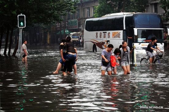 People cross a waterlogged street in Tiexi District of Shenyang, capital of northeast China's Liaoning Province, Aug. 16, 2013. Some parts of Shenyang were waterlogged due to downpour caused by thunderstorms Friday. (Xinhua/Huang Jinkun)
