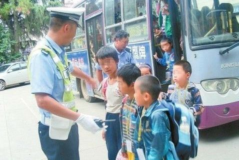 A police officer counts school students coming off a bus he intercepted in Kunming, Yunnan Province on Wednesday.