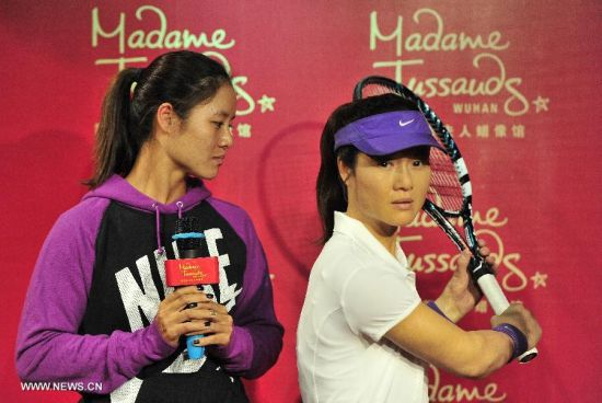 China's top women tennis player Li Na (L) looks at her wax figure at the Madame Tussauds in Wuhan, capital of central China's Hubei Province, Sept. 12, 2103. Li on Thursday became the first Asian sport star to have a wax figure in the Wuhan Madame Tussauds. (Xinhua)