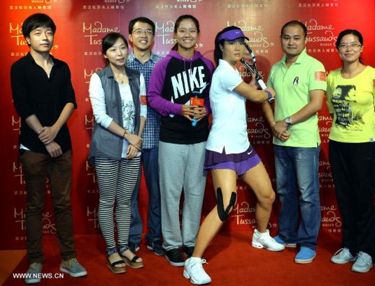China's top women tennis player Li Na (C) poses for photo with her wax figure and fans at the Madame Tussauds in Wuhan, capital of central China's Hubei Province, Sept. 12, 2103. Li on Thursday became the first Asian sport star to have a wax figure in the Wuhan Madame Tussauds. (Xinhua)