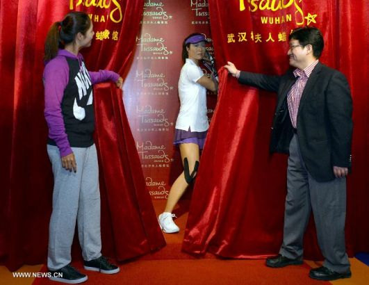 China's top women tennis player Li Na (L) attends the unveiling ceremony of her wax figure at the Madame Tussauds in Wuhan, capital of central China's Hubei Province, Sept. 12, 2103. Li on Thursday became the first Asian sport star to have a wax figure in the Wuhan Madame Tussauds. (Xinhua)