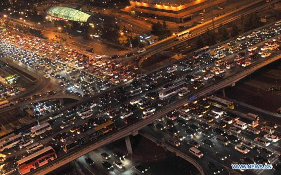 Photo taken on Sept. 22, 2013 shows the crossroad of Guomao area at the evening rush hour in Beijing, capital of China. More than 150 Chinese cities including Beijing observed World Car Free Day on Sunday to fight air pollution, but the capital remained clogged with traffic jams. (Xinhua/Gong Lei)