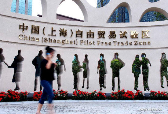 A pedestrian walks past a sculpture at the free trade zone (FTZ) in Shanghai, east China, Sept. 26, 2013. China will officially launch the pilot FTZ in Shanghai on Sept. 29, taking a solid step forward to boost reforms in the world's second-largest economy. Covering almost 29 square kilometers, the zone will be created modeled on existing free trade businesses in the country's economic hub. (Xinhua/Chen Fei)