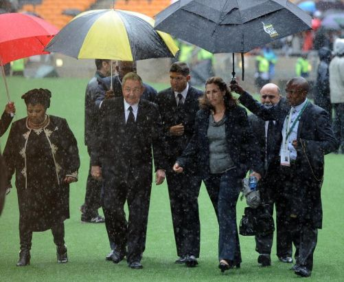 Raul Castro (uncer umbrella) arrives for Nelson Mandela's memorial service at the Soccer City stadium Soweto on December 10, 2013