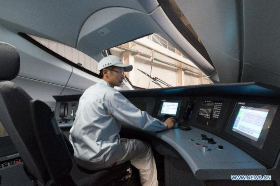 A worker conducts the static electricity test on a CRH380 high-speed train in the manufacturing plant of Qingdao Sifang Co. Ltd., in Qingdao, east China's Shandong Province, Jan. 3, 2014.