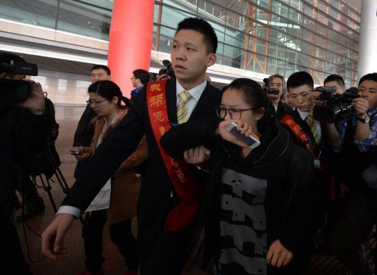 A crying woman is escorted to a bus for relatives at Beijing Airport