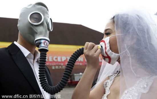 A couple in wedding attire wear masks during an anti-smog campaign on Foreigner Street in Chongqing, Feb 28, 2014. The event was an appeal for reducing air pollution and increasing environmental protection. [Photo/icpress.cn]