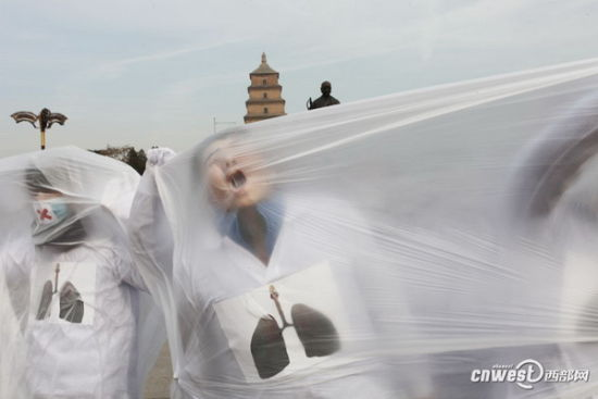 Volunteers from the Xi'an Academy of Fine Arts fake coughed in white plastic bags on Dec 5, 2013. On the International Volunteer Day, 23 voluntary college students gave street performances in the bustling parts of Xi'an, Shannxi province, to advocate low carbon against smog. [Photo/cnwest]