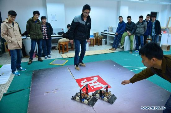 Students from a robot design team demonstrate the award-winning projects of the latest China Robot Competition in Nantong University, Nantong, east China's Jiangsu Province, March 11, 2014. (Xinhua/Shen Peng)
