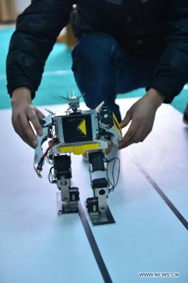 A student from a robot design team demonstrates a robot which got a prize in the latest China Robot Competition in Nantong University, Nantong, east China's Jiangsu Province, March 11, 2014. (Xinhua/Shen Peng)