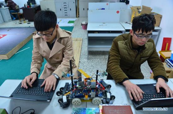 Students from a robot design team type in running program for robots in Nantong University, Nantong, east China's Jiangsu Province, March 11, 2014. Students demonstrate the award-winning projects of the latest China Robot Competition at school's laboratory on Tuesday. (Xinhua/Shen Peng)