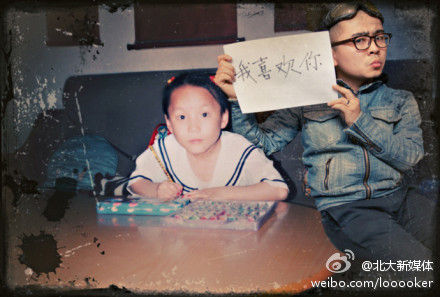 Hiding himself behind the girl, Wang holds a sign reading