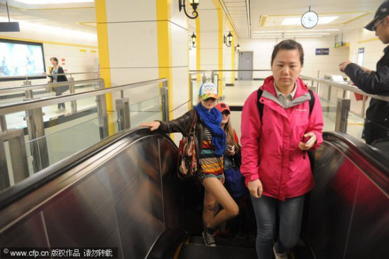 A passenger minus her pants, left, rides a subway station escalator in Harbin, northeast China's Heilongjiang province, on World Earth Day, April 22, 2014. The
