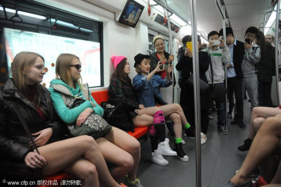 A passenger, fourth from left, takes a selfie while going without pants on a Harbin subway on World Earth Day, April 22, 2014. [Photo/CFP]