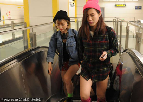 Two passengers without pants, leave an escalator at a Harbin subway station on World Earth Day, April 22, 2014. The