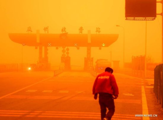 A man walks in a sandstorm at Guazhou toll station in Jiuquan, northwest China's Gansu Province, April 23, 2014. Parts of Gansu was hit by a sandstorm Wednesday afternoon, which reduced visibility to less than 50 meters, according to the provincial meteorological center. (Xinhua/Nie Jianjiang)
