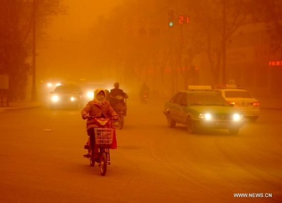 A lady rides in a sandstorm in Dunhuang, northwest China's Gansu Province, April 23, 2014. Parts of Gansu was hit by a sandstorm Wednesday afternoon, which reduced visibility to less than 50 meters, according to the provincial meteorological center. (Xinhua/Nie Jianjiang)
