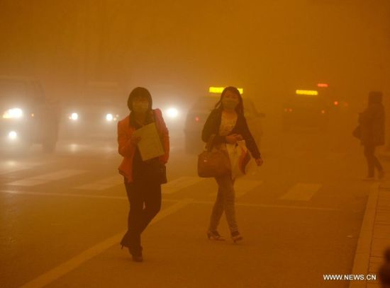 Girls wear masks while walking in a sandstorm in Dunhuang, northwest China's Gansu Province, April 23, 2014. Parts of Gansu was hit by a sandstorm Wednesday afternoon, which reduced visibility to less than 50 meters, according to the provincial meteorological center. (Xinhua/Nie Jianjiang)