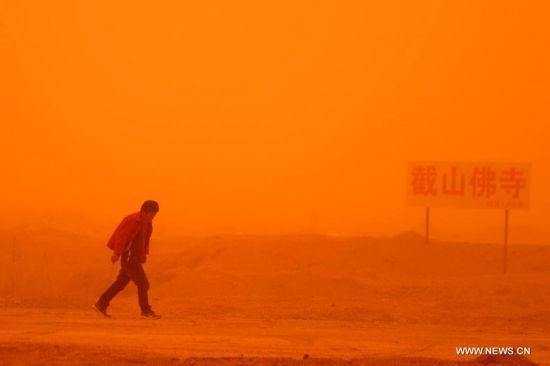 A man walks in a sandstorm on the outskirt of Guazhou, Jiuquan, northwest China's Gansu Province, April 23, 2014. Parts of Gansu was hit by a sandstorm Wednesday afternoon, which reduced visibility to less than 50 meters, according to the provincial meteorological center. (Xinhua/Nie Jianjiang)