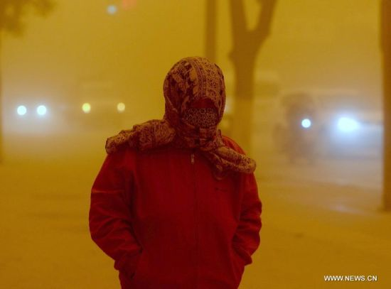 A pedestrian wears a kerchief on her head to shelter from a sandstorm in Dunhuang, northwest China's Gansu Province, April 23, 2014. Parts of Gansu was hit by a sandstorm Wednesday afternoon, which reduced visibility to less than 50 meters, according to the provincial meteorological center. (Xinhua/Nie Jianjiang)