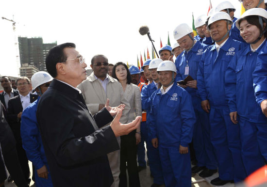 Chinese Premier Li Keqiang, accompanied by Ethiopian Prime Minister Hailemariam Desalegn, speaks to workers and technicians during a visit to a light railway project in Addis Ababa, capital of Ethiopia, May 5, 2014. (Photo source: gov.cn)
