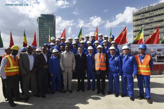 Chinese Premier Li Keqiang (C) and Ethiopian Prime Minister Hailemariam Desalegn (5th L) pose for a group photo with workers and technicians during a visit to a light railway project in Addis Ababa, capital of Ethiopia, May 5, 2014. (Xinhua/Li Xueren)
