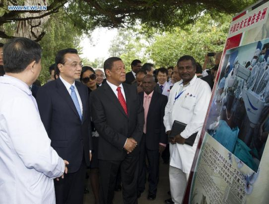 Chinese Premier Li Keqiang (2nd L) and Ethiopian President Mulatu Teshome (3rd L) look at the introduction of the free ophthalmological service