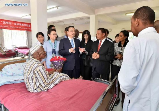 Chinese Premier Li Keqiang (3rd L front) and Ethiopian President Mulatu Teshome (3rd R) visit a patient who has received a free cataract surgical operation of the program