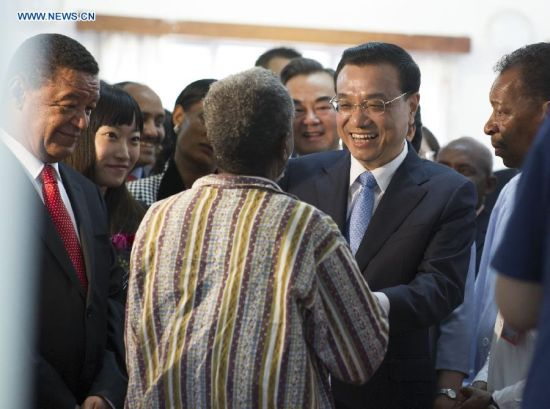 Chinese Premier Li Keqiang (2nd R) and Ethiopian President Mulatu Teshome (1st L) visit a patient who has received a free cataract surgical operation of the program