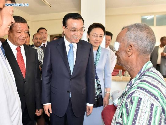 Chinese Premier Li Keqiang (C) and Ethiopian President Mulatu Teshome (2nd L) visit a patient who has received a free cataract surgical operation of the program