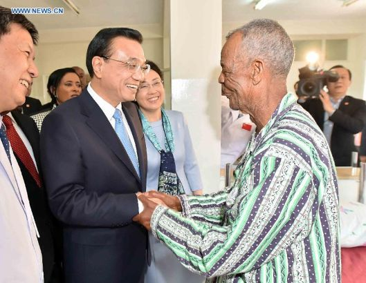 Chinese Premier Li Keqiang (2nd L) visits a patient who has received a free cataract surgical operation of the program