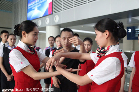 Stewardesses-to-be learn the basic movements from Tu. [Photo/IC]