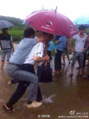 An official riding on another person through a flooded area