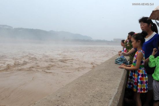 Tourists watch water gushing out from the Xiaolangdi Reservoir on the Yellow River during a sand-washing operation in Luoyang, central China's Henan Province, June 30, 2014. The on-going operation works by discharging water from the reservoir to clear up the sediment in the Yellow River, the country's second-longest waterway. This year, the sand-washing operation will be jointly conducted in Xiaolangdi Reservior, Sanmenxia Reservior and Wanjiazhai Reservoir, an effort to make speeding currents carry tons of sand into the sea. The Yellow River has been plagued by an increasing amount of mud and sand. Each year, the river bed rises as silt deposits build up, slowing the water flow in the lower reaches. (Xinhua/Zhu Xiang)