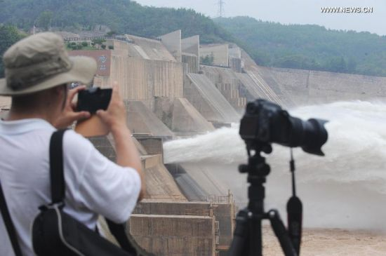 A tourist takes photo of water gushing out from the Xiaolangdi Reservoir on the Yellow River during a sand-washing operation in Luoyang, central China's Henan Province, June 30, 2014. The on-going operation works by discharging water from the reservoir to clear up the sediment in the Yellow River, the country's second-longest waterway. This year, the sand-washing operation will be jointly conducted in Xiaolangdi Reservior, Sanmenxia Reservior and Wanjiazhai Reservoir, an effort to make speeding currents carry tons of sand into the sea. The Yellow River has been plagued by an increasing amount of mud and sand. Each year, the river bed rises as silt deposits build up, slowing the water flow in the lower reaches. (Xinhua/Zhu Xiang)
