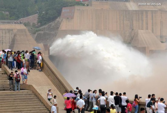 Tourists watch water gushing out from the Xiaolangdi Reservoir on the Yellow River during a sand-washing operation in Luoyang, central China's Henan Province, June 30, 2014. The on-going operation works by discharging water from the reservoir to clear up the sediment in the Yellow River, the country's second-longest waterway. This year, the sand-washing operation will be jointly conducted in Xiaolangdi Reservior, Sanmenxia Reservior and Wanjiazhai Reservoir, an effort to make speeding currents carry tons of sand into the sea. The Yellow River has been plagued by an increasing amount of mud and sand. Each year, the river bed rises as silt deposits build up, slowing the water flow in the lower reaches. (Xinhua/Li An)