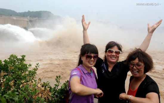 Tourists pose for photos near the Xiaolangdi Dam in Jiyuan, central China's Henan Province, June 30, 2014. The artificial water cascades generated by the Xiaolangdi Dam on the Yellow River are feasts for the eyes for tourists when the dam does its annual de-sedimentation between late June and early July. (Xinhua/Li An)