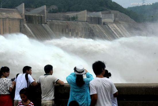 Tourists look at water cascades generated by the Xiaolangdi Dam on the Yellow River in Jiyuan, central China's Henan Province, June 30, 2014. The artificial water cascades generated by the Xiaolangdi Dam on the Yellow River are feasts for the eyes for tourists when the dam does its annual de-sedimentation between late June and early July. (Xinhua/Li An)