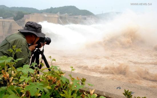 A tourist takes photos of the Xiaolangdi Dam and its water cascades in Jiyuan, central China's Henan Province, June 30, 2014. The artificial water cascades generated by the Xiaolangdi Dam on the Yellow River are feasts for the eyes for tourists when the dam does its annual de-sedimentation between late June and early July. (Xinhua/Li An)