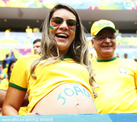 A pregnant Brazil fan laughs during the group match against Cameroon in Brasilia, June 23, 2014. [Photo/IC]