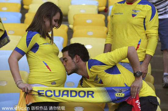 An Ecuadorean fan kisses his unborn child during a group match against France in Rio de Janeiro, June 25, 2014. [Photo/IC]