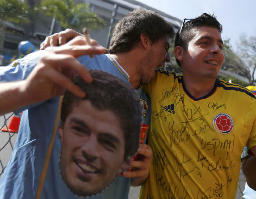 A Uruguay fan jokes with a rival Colombian fan of Colombia before their round of 16 game, June 28, 2014. [Photo/Agencies]